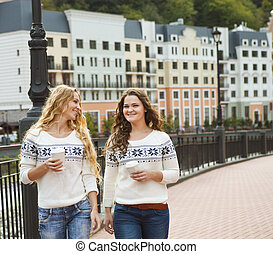 Two casual happy women having a conversation while walking...