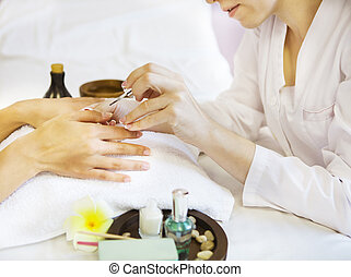 Woman in nail salon receiving manicure by beautician