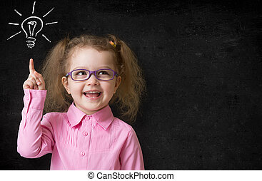 kid in glasses with idea lamp on school chalkboard in...