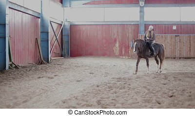 Young woman ride a horse  at the stable.