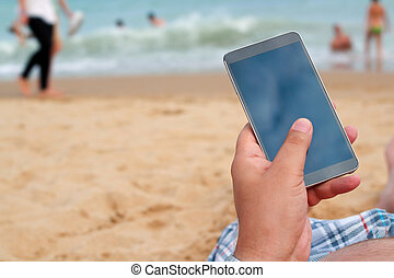 Man holding a mobile phone. internet connection on the beach