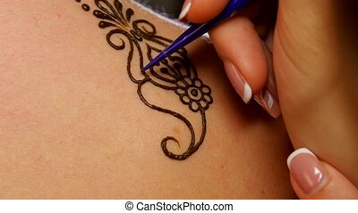 Process of decorating womans back with henna tattoo, mehendi, on black