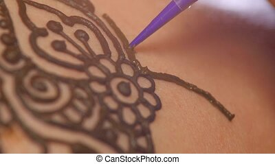 Process of decorating womans back with henna tattoo, mehendi, on black, dynamic change of focus
