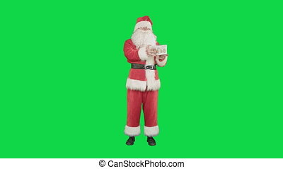 Happy Santa Claus carrying gifts on a Green Screen Chrome Key
