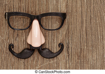 fake mustache, nose and eyeglasses on a wooden surface - a...