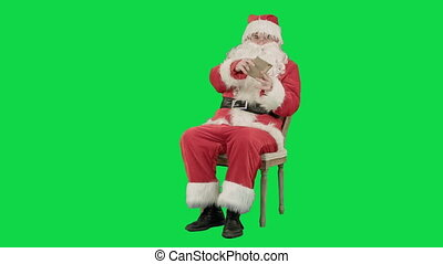 Santa Claus sitting on chair with letters in hands on a Green Screen Chrome Key