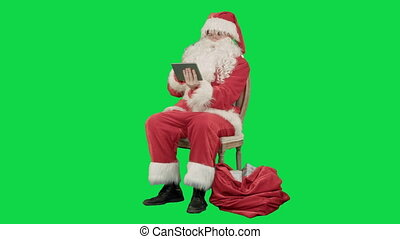 Santa Claus using tablet computer to surf internet and communicate in social media with children on a Green Screen Chrome Key