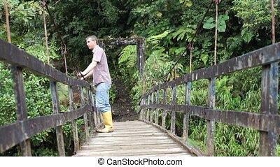 Man on Hanging Bridge Coming Low - Low angle shot of a...