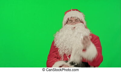 Santa Claus calling with a mobile phone on a Green Screen Chrome Key