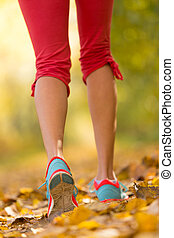 Close up of feet of female runner running in autumn leaves....