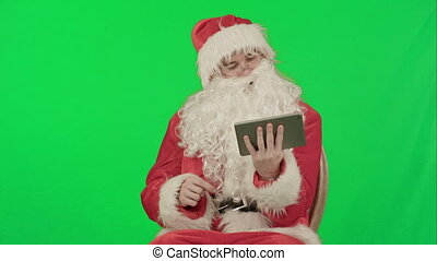 Santa listening music and touching tablet on a Green Screen...