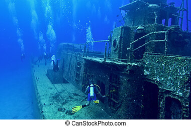 scuba divers explore a wreck - A group of divers are...