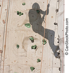Shadow Climbing Rock Wall - A shadow using a rope to climb a...