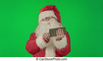 Cheerful Santa Claus is holding a tablet in his hands on a Green Screen Chrome Key