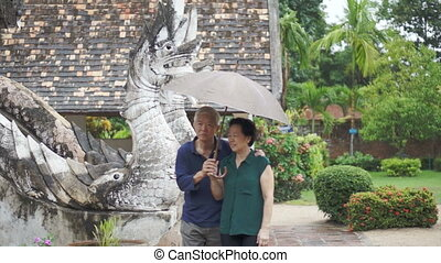 Asian senior couple under umbrella - Video of Asian senior...