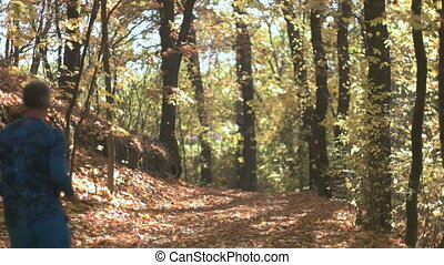Fall Season in the Forest - Young adult running on the...