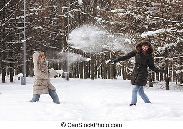 Snowball fight - Two friend women at snowball fight in...
