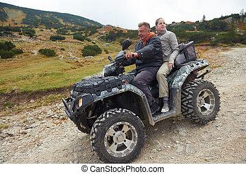 couple drive atv quad bike in mountain nature
