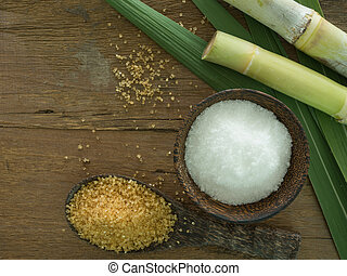 sugarcane - granulated sugar with sugarcane stems on wooden...