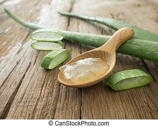 aloe vera gel on wooden spoon with aloe vera on wooden table
