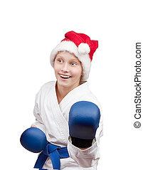 Girl standing in rack of karate - Girl in hat of Santa Claus...