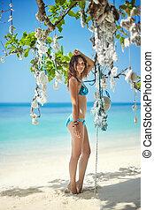 beautiful girl in bikini posing on the tropical beach
