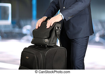 young businessman in a modern stylish suit with luggage in...