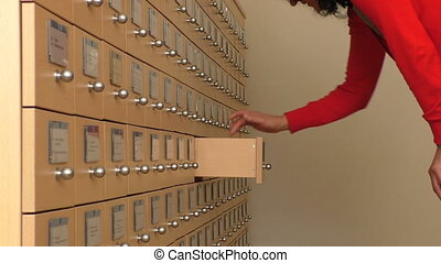 Woman searching for a file - Woman in the office searching...