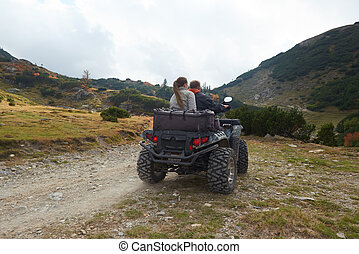 couple drive atv quad bike in mountain nature
