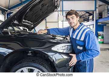 Car mechanic under the hood - Portrait of a smiling car...