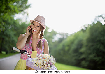 Communication - Beautiful girl on a bicycle talking on the...