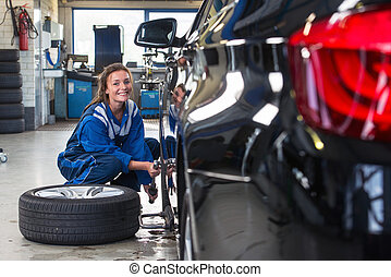Female service mechanic changing the front tire of a car