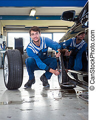 Changing winter tires - Mechanic, mounting winter tires on a...