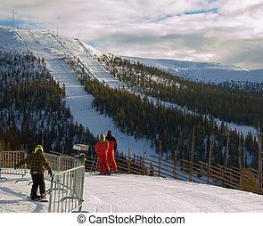Overlooking a steep ski run - skiers overlooking a straight...