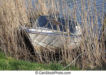 Sunken recreational boat half underwater