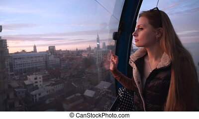 Travel: beautiful young woman tourist looking through the...