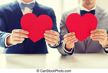 close up of male gay couple holding red hearts - people,...