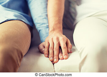 close up of happy male gay couple holding hands - people,...