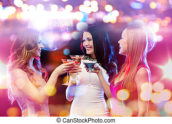 smiling women with cocktails at night club - holidays,...