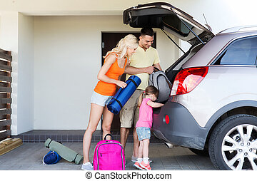 happy family packing things to car at home parking -...