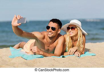 happy couple in swimwear walking on summer beach - love,...