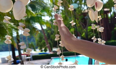 Hand playing with sea shell mobile hand craft by the sea