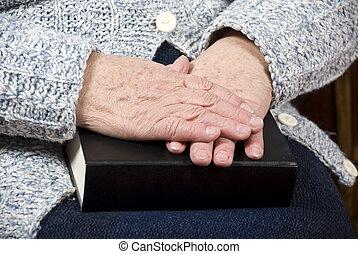 Elderly hands on bible