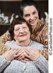 Granddaughter giving a hug to her grandma - Granddaughter...