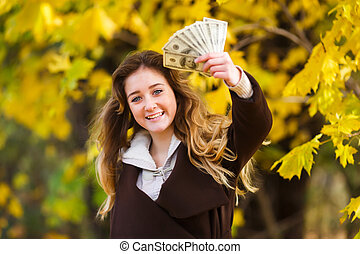 The first teenager's pay - Happy young smiling girl holds...