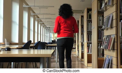 Woman sits down in the library - Woman with dark curly hair...