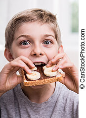 Kid eating with appetite - Smiling kid eating sweet sandwich...