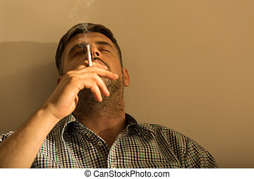 Man smoking a cigarette - Portrait of man smoking a...