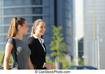 Businesswomen walking and talking in the street - Two happy...