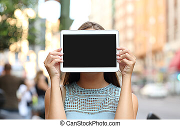 Showing a blank tablet screen covering her face - Woman...